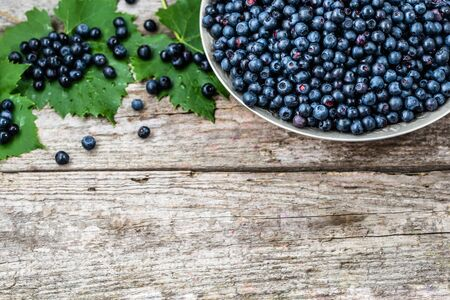 Fresh blueberries in basket on wooden table, ripe fruits from forest on farmer market, copy space, top view
