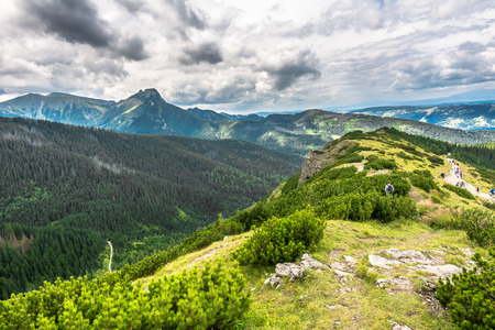 Carpathian mountain range, view on hill in Tatras and hiking trail with people in the distant