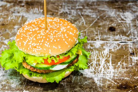 Tasty hamburger with beef  and vegetables on rusty sheet metal background