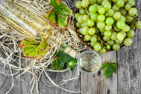 White wine bottle and glasses of wine from green grape. Seasonal homemade wine in wooden pantry. Stock Photo