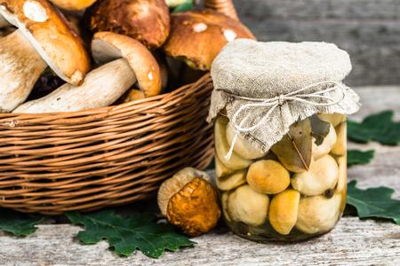Marinated mushrooms - boletus pickled in jar on rustic table, preserves preparing