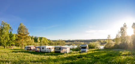 Caravans and camping on the lake. Family vacation outdoors, travel concept 免版税图像