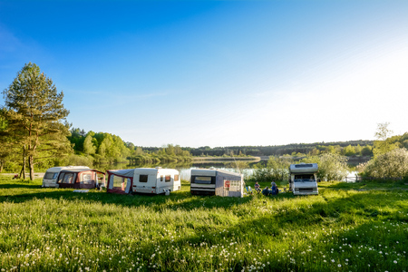 Caravans and camping on the lake. Family vacation outdoors, travel concept Фото со стока