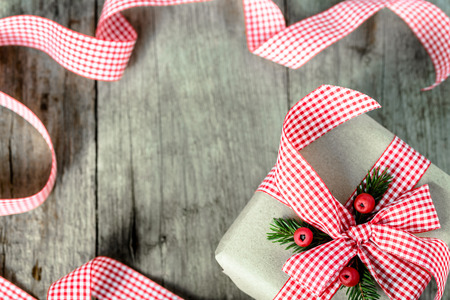 Christmas gift with ribbon on wooden rustic table, overhead