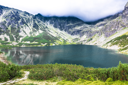 Mountain lake landscape with hiking trail, National Park in Tatra Mountains Stock Photo