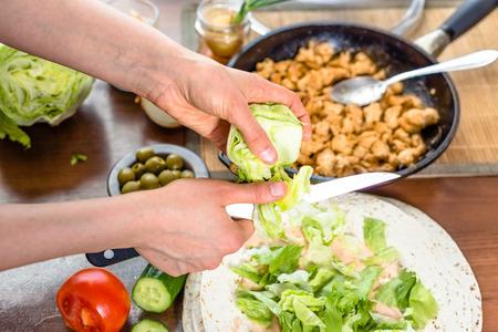 Cuisine rapide. Mains préparant une tortilla wrap avec salade de poulet et de légumes, garniture de gyros kebab. Banque d'images - 83750790