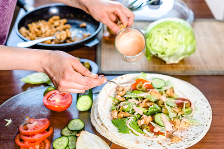 Fast food cooking. Hands preparing tortilla wrap with chicken and vegetable salad, kebab gyros filling.