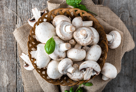 Fresh champignon mushrooms in a basket on wooden table, overhead Stock fotó - 84288192