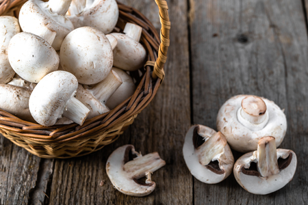 Fresh champignon mushrooms in a basket on wooden table, overhead Imagens