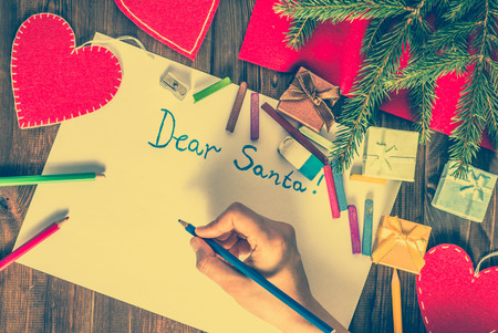 christmas gifts: Hand writing letter to Santa Claus. Christmas card with decorations, overhead