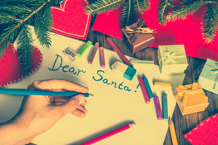 Hand writing letter to Santa Claus. Christmas card with decorations, gift boxes and spruce.
