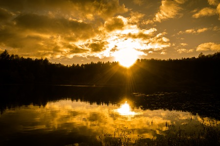 Lake landscape in autumn, sunset sky and sunbeams over forest, silhouette of wild nature