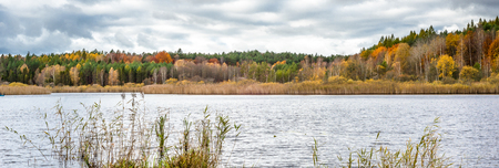 Autumn forest over lake, autumn panoramic vista with colorful trees and cloudy sky Stock Photo
