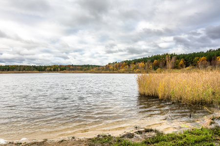 Cloudy autumn landscape with lake and forest