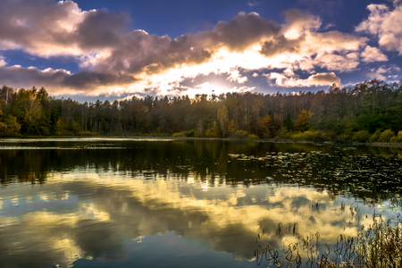 Sunset sky over lake, sun fall in the forest, autumn landscape