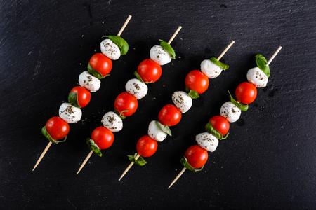 イタリア料理-カプレーゼサラダ-トマト、モッツァレラ、バジルの串焼き、地中海ダイエットコンセプト 写真素材 - 85288261