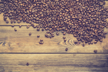 Black coffee beans background, coffees grain on wooden table, overhead Фото со стока