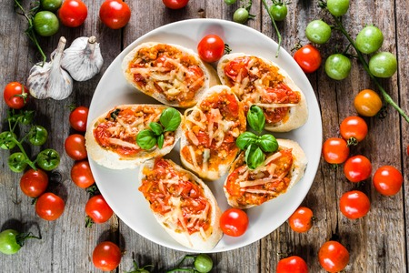 Italian bruschetta with tomatoes and basil, spicy appetizers, top view on plate for party or sharing with friends