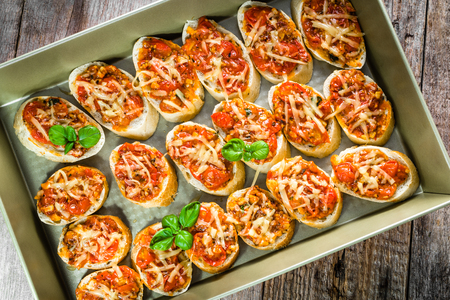 Plate with food, italian bruschetta with tomatoes and basil, spicy appetizers for party or sharing with friends