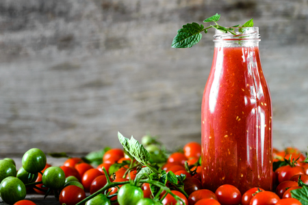 ketchup bottle: Bottle of tomato juice and fresh tomatoes on wooden background, organic healthy food concept