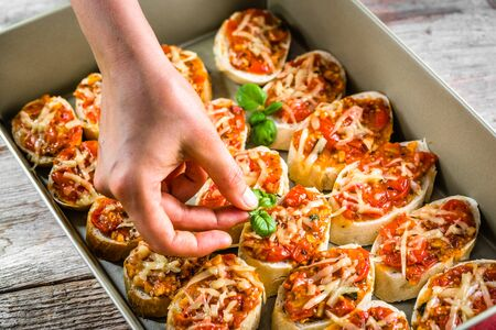 Chef cook preparing italian bruschetta with tomatoes, basil and cheese, garnishing food, cooking homemade appetizer for the party Stock Photo