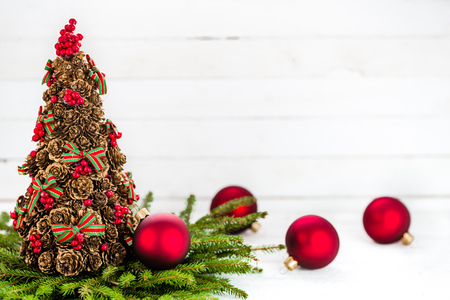 Christmas background with decorations - red balls and fir twigs on white wooden table