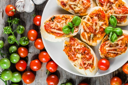 Traditional bruschetta with tomatoes and basil, italian appetizers, top view on plate for party or sharing with friends Stock Photo