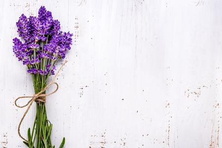 Fresh flowers of lavender bouquet, top view on white wooden background Foto de archivo