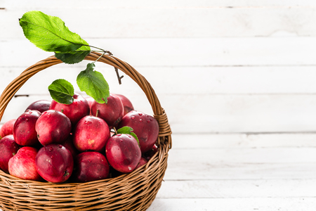 Red apples on table in the basket, pile of fresh apple fruit on white background