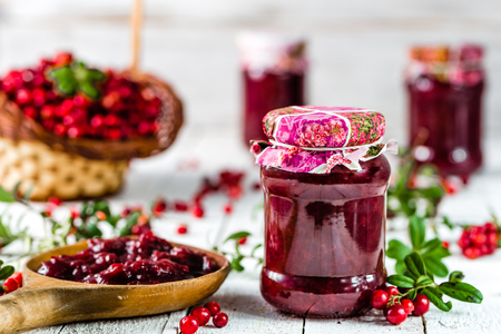 Cranberry jam in a jar on white wooden table