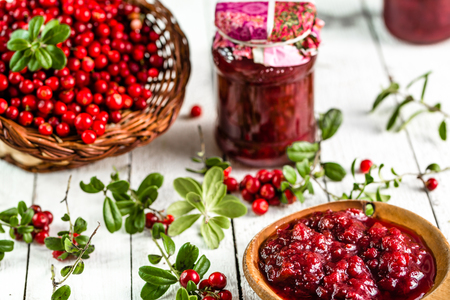 Spoon and jars of jam with cranberry on white wooden background Stock Photo