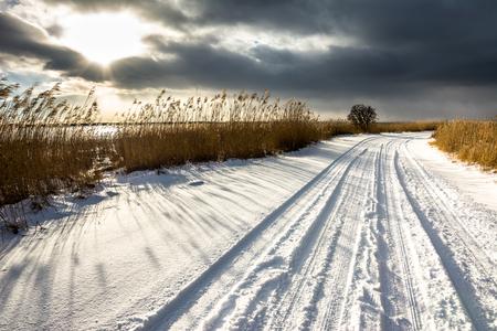Winter road, landscape, sun on dark sky, moody scenery in nature