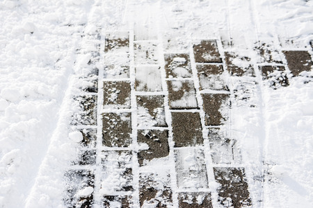 Background of snow on footpath in winter, texture of paving