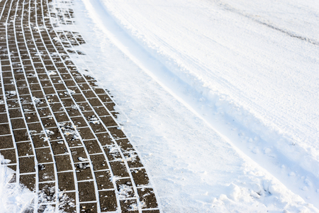 Background with snow on road and sidewalk in winter, texture