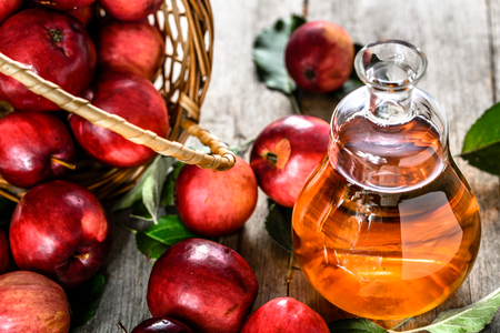 Wine bottle or apple cider vinegar, healthy detox drink with organic red apples on table