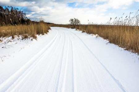 tire tracks: Snow on road, winter landscape with moody sky before sunset over lake Stock Photo