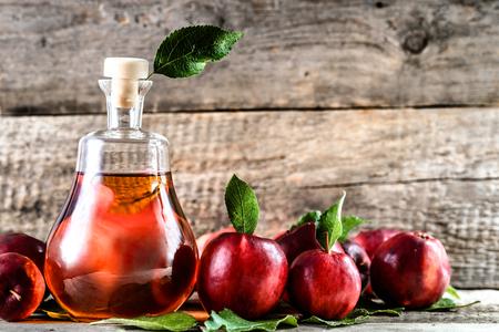 ワインボトルやリンゴサイダー酢、テーブルの上に有機赤いリンゴと健康的なデトックスドリンク 写真素材