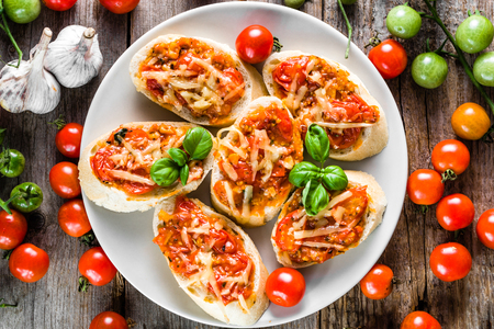 Traditional bruschetta with tomatoes and basil, spicy italian snack, overhead on plate for party and sharing with friends Stock Photo