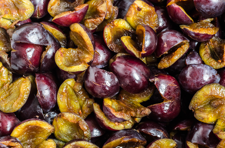 Pitted prune plums background.