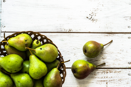 Fresh pears in the basket. Organic fruits on rustic wooden background.
