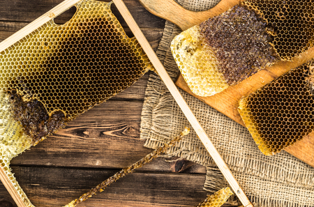 drizzler: Honeycombs with honey on rustic wood background covered with jute sackcloth, top view.