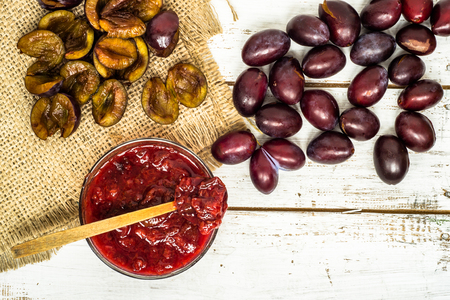 Mermelada de ciruela en un recipiente en la mesa de madera, comida orgánica natural - conserva casera para el invierno
