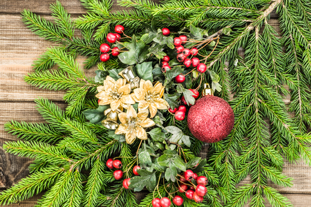 Christmas background with ornaments on fir branches, holiday decoration on wooden boards, top view