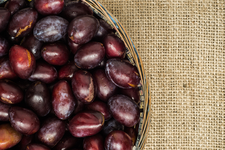 Fresh prune plums in the basket on rustic background.