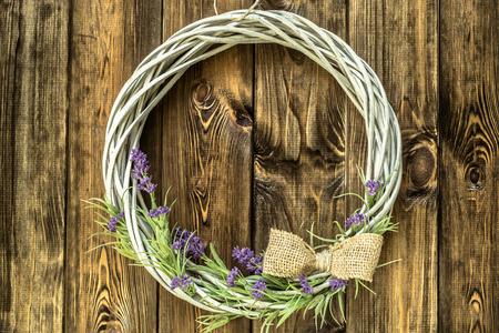 木製の素朴な背景にラベンダーの花と編組籐のリース。プロバンス風。 写真素材