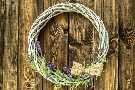 Braided wicker wreath with lavender flowers on wooden rustic background. Provencal style.