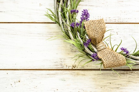 Braided wicker wreath with lavender flowers on vintage wood background. Provencal style. Stock fotó