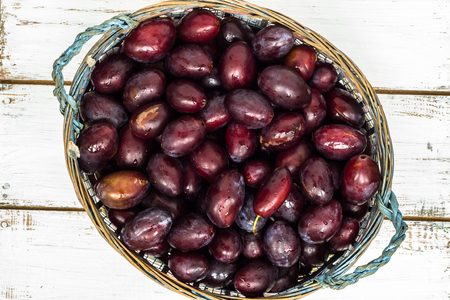 Fresh prune plums in the basket on wooden background.