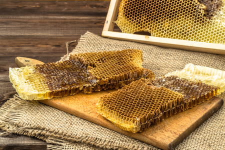 Honeycombs with honey on rustic wood background covered with jute sackcloth, selective focus.
