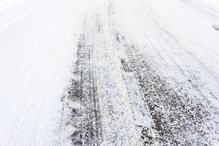 Country road in winter , asphalt covered snow with tire tracks, transportation concept Stock Photo